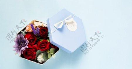 蓝色背景上装满花的礼物盒